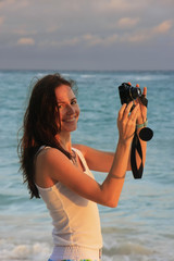 Woman taking picture at sunrise on a beach
