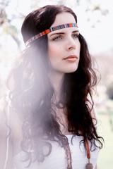 Junge attraktive brunette Frau mit Stirnbadn im Sommer im Park