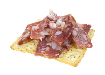 Cut pieces of sopressata on wheat cracker