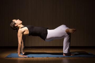 Young beautiful woman do yoga posing, low key
