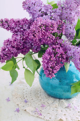 Beautiful lilac flowers in turquoise vase