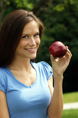 Attractive Woman Smiling in Park with Red Delicious Apple