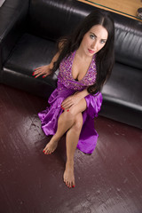 Stunning Woman on Black Leather Sofa in Purple Evening Gown