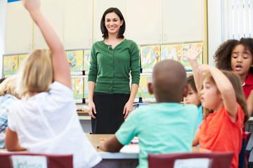 Teacher Talking To Elementary Pupils In Classroom