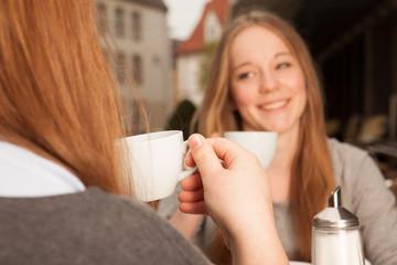 Zwei junge Damen trinken Kaffee / Tee