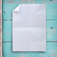 Wrinkled white paper with grunge wood background.