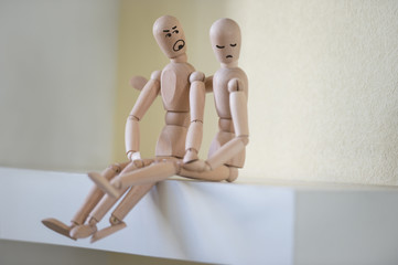Wooden people sitting at home in quarrel. People relationship co