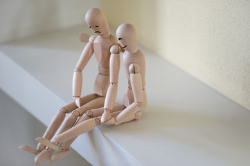 Wooden people sitting at home and supporting each other. People