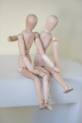 Wooden people sitting at home and hugging. People relationship c