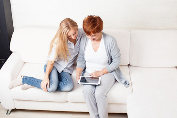 Mother and daughter wiht tablet at sofa