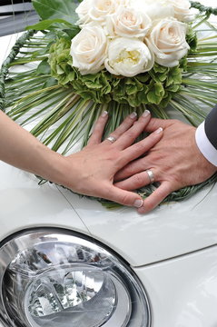 Wedding, Bride and Groom holding hands on the Vintage car