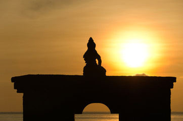 Silhouette of sitting Buddha against rising sun