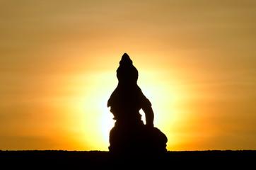 Sitting Buddha against rising sun