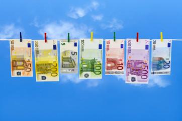 Euro-Geldscheine hängen an Wäscheklammern