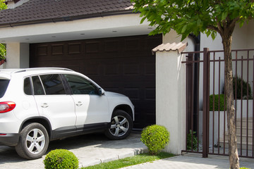 White car in front of the house waiting to enter in the garage