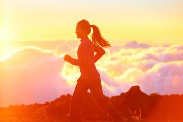 Running - woman runner jogging at sunset