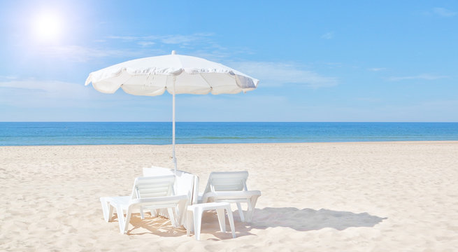 Beautiful white beach umbrella and sun bed on the beach. For the