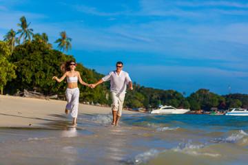 running couple on a tropical beach
