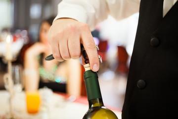 Waiter uncorking a wine bottle