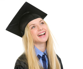 Portrait of smiling young woman in graduation gown looking on co