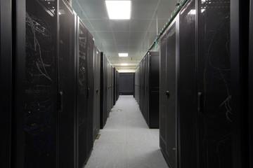 Telecommunications equipment in black racks in server room.