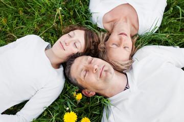 familie liegt entspannt im grünen