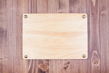 Wooden sign board with nails on planks wall background