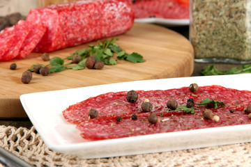 Tasty salami on plate and board on wooden table close-up