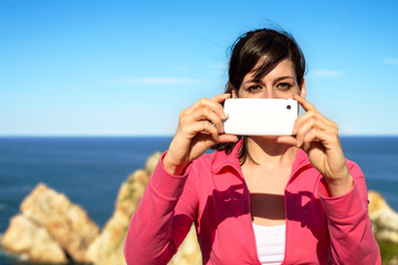 Woman taking photo with cellphone on summer