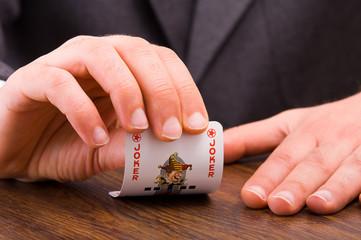 Businessman showing joker card.