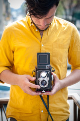 hipster young man with old camera