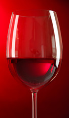 Glass of wine on red background