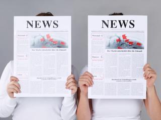 Two girls reading newspaper