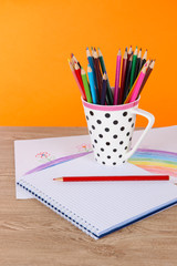 Colorful pencils in cup on table on orange background