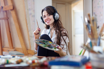 Long-haired woman in headphones  paints with oil colors