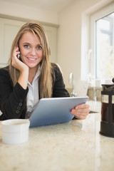 Woman phoning and holding a tablet