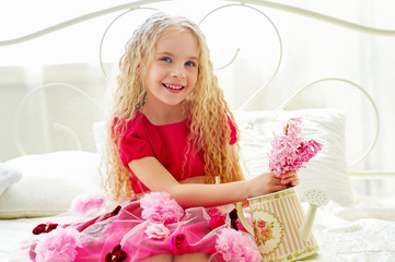 Beautiful little girl in pink dress sitting on the bed