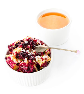 Fruit fresh crumble dessert in a white bowl with a cup of tea  o