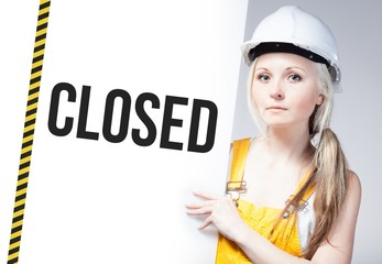 Worker holding closed sign on information board