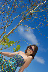 young beautiful happy woman on tropical blue sky background