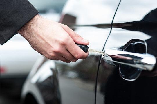 Man inserting car key into the door lock