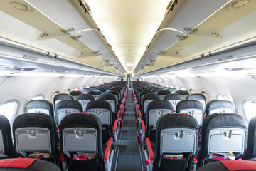 Vanishing row of black and red seats in airplane.