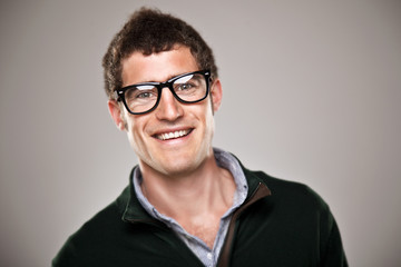 Portrait of a normal boy smiling over grey background.