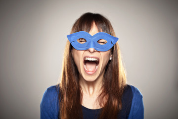 Portrait of a normal girl screaming with a blue mask
