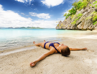 Young beautiful woman is relaxing on sand by the sea