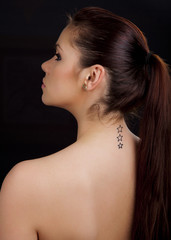 Portrait of a beautiful woman with tattoo on her back