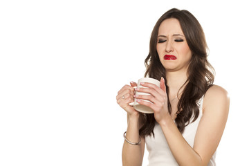 girl makes a disgusting face and refusing to drink his tea