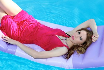 girl is laying on the matress in the pool
