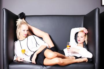 weibliche Models posieren in einem Ledersessel