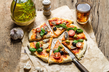 Homemade pizza served on old wooden table